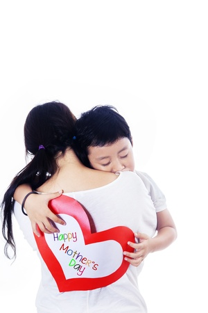 Boy hug mother holding love card on white background photo