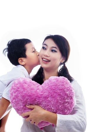 Boy kiss mother holding heart shape pillow on white background photo