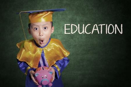 scholar: Boy holding piggybank shock on education fees  Stock Photo