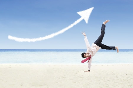 Businessman is dancing under increase arrow sign cloud at beach photo