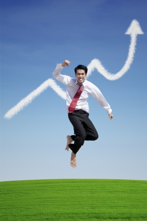 asian businessman: Businessman jumping happily upon successful project, under increase arrow sign cloud