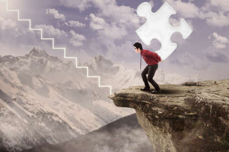 Businessman is walking up with puzzle on mountain with virtual stairs photo