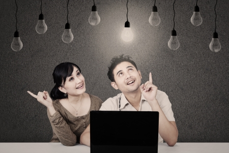 asian couple: Asian students with laptop looking at lit bulb Stock Photo