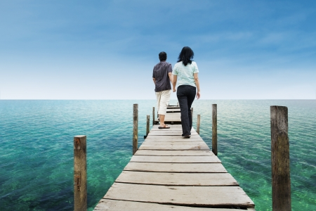 Couple is walking on top of a wood deck near the beach photo