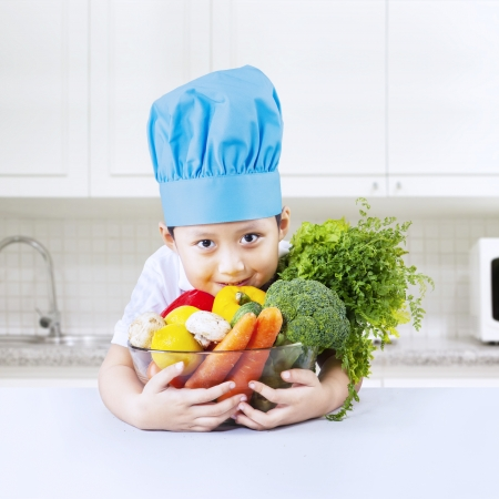 toque: asian boy with vegetables in the kitchen