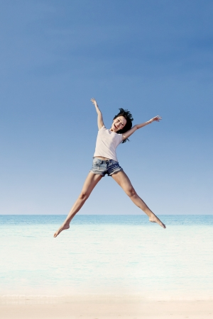 Girl jumping under blue sky at the beach photo