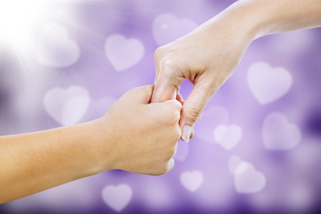 reaching: Hand gestures of a mother giving her hand to her child on purple love shape defocused lights