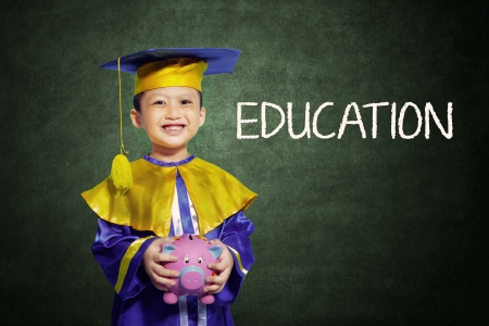 educated: Happy scholar dressed toddler carrying a piggybank
