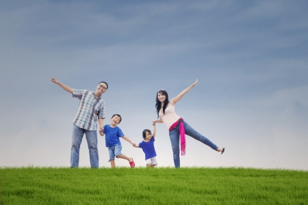Happy Asian family on the green hill photo