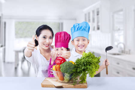 brocoli: Happy kids chef with their mother preapring vegetable at home