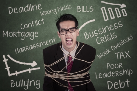 Angry businessman tied with rope in classroom photo
