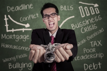 Angry businessman with hands chained at classroom photo