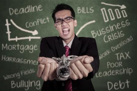 empresario enojado: Hombre de negocios enojado con las manos encadenadas en el aula