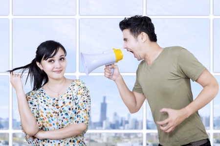 Boyfriend yelling with a megaphone to his girlfriend photo
