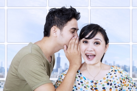 Man whispering a good news to his spouse photo