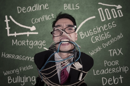 Close-up crazy businessman tied in cable and rope at class photo
