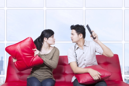 red sofa: Couple fight on red sofa in apartment Stock Photo
