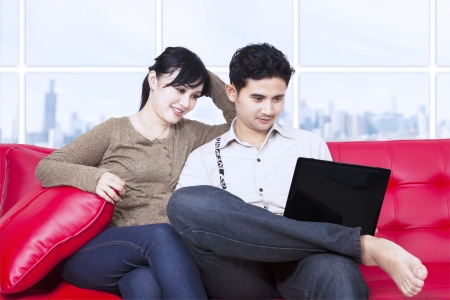 Couple looking at laptop in apartment on red sofa photo