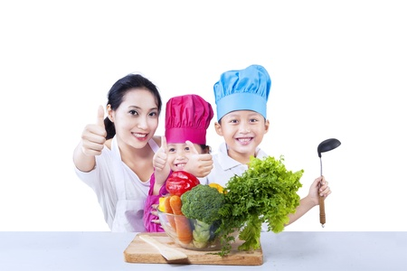 Happy family chef prepare vegetable meal on white background Stock Photo - 19552877