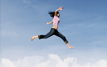 woman jumping: Active woman is jumping over the clouds