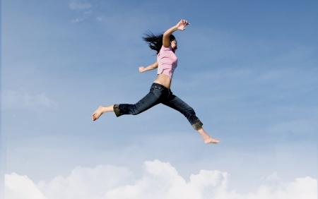 pulando: Mulher ativa � saltar sobre as nuvens Banco de Imagens