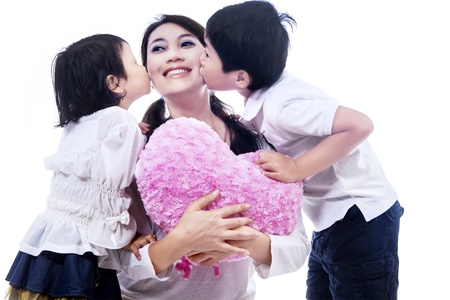 Happy mom kissed by children on white background photo