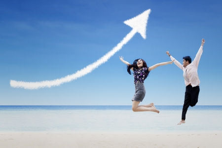 businessman jumping: Happy business partners jump under increase arrow sign cloud at beach
