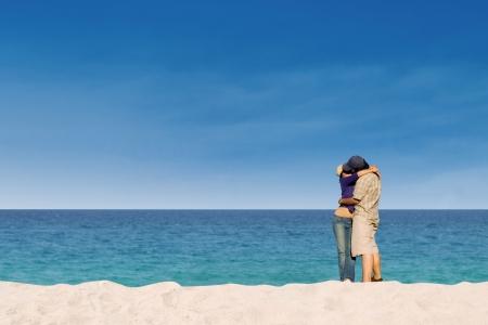 whitehaven: Romantic couple kissing on Whitehaven beach, Queensland, Australia