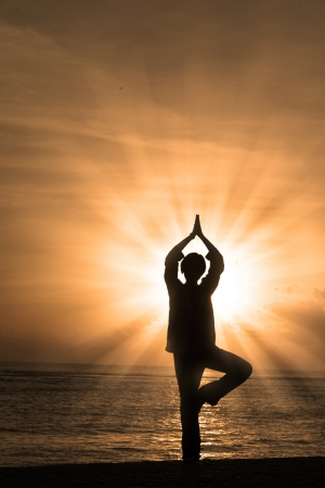 Beautiful silhouette of a woman practicing yoga at beach photo
