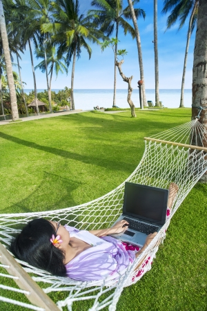 Asian girl work in hammock with laptop at Bali beach, Indonesia photo