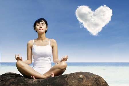 Asian woman meditating at beach under love cloud Stock Photo - 22632547