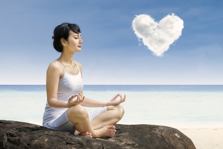 Attractive woman exercise yoga under love cloud at beach Stock Photo - 22632544