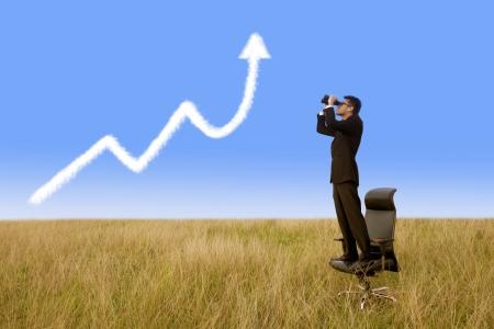 Businessman using binoculars looking growth graph cloud under blue sky photo