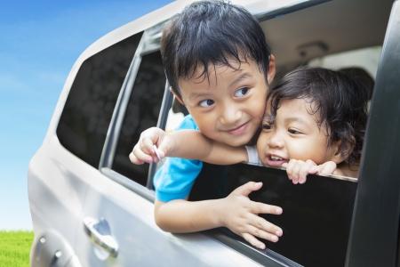road trip: Cute sibling in car during road trip Stock Photo