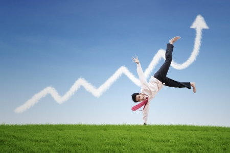 growing up: Happy businessman dance on profit chart cloud under blue sky Stock Photo