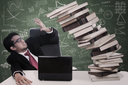 Stress businessman with falling books and laptop at classroom photo