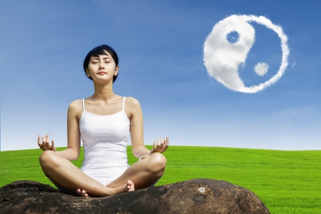 contentment: Exercise yoga outdoor under ying yang cloud as the symbol of harmony Stock Photo