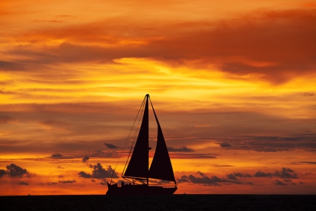Amazing sunset landscape and sailing ship on the ocean photo