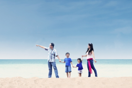 Asian family enjoying their holiday at white sand beach photo
