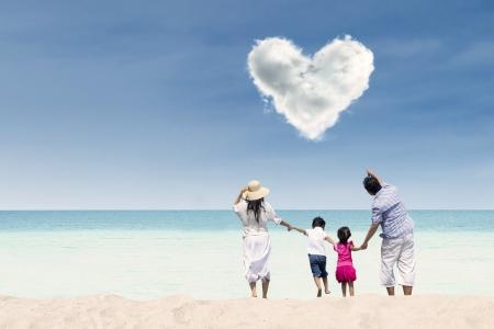 familia viaje: Familia feliz corriendo hacia la playa bajo las nubes del amor Foto de archivo