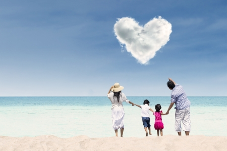 Happy family running towards the beach under love cloud photo