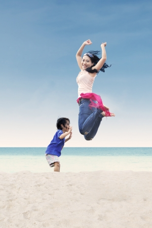 Asian mother jumping with her daughter at beach photo
