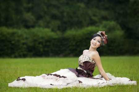 Attractive bride sitting on green field, looking at the camera