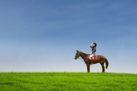 Attractive female jockey riding horse at green field photo