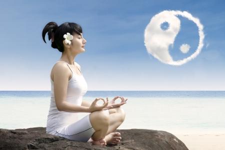 Girl practising yoga at beach with ying yang cloud Stock Photo - 19667304