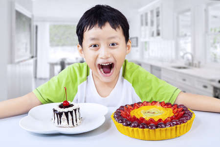 Boy laughing with fruit desserts at home photo