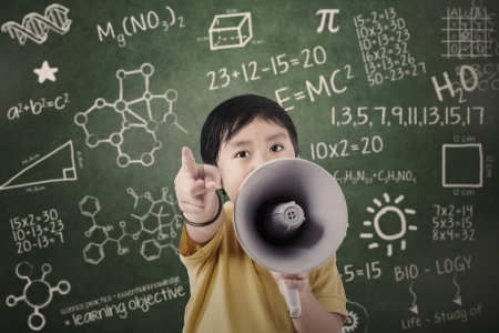 protest: Boy with speaker at classroom with written formula and shapes Stock Photo