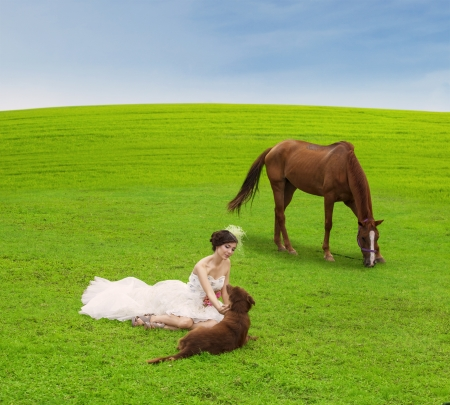 Beautiful bride is playing with horse and dog on green field photo