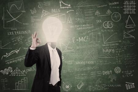 Smart teacher with lightbulb head in class photo