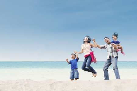 the place is outdoor: Cheerful family jumping at white sand beach Stock Photo